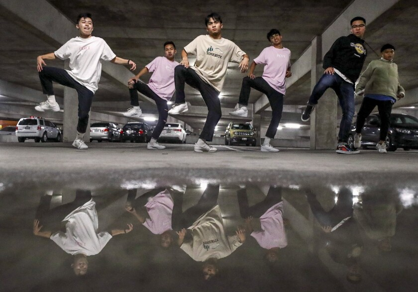 A hip-hop dance group is reflected in a puddle as they perform during an end of the year choreography project put on by the SDSU Vietnamese Student Organization Modern, a collegiate hip-hop dance troupe, in a parking garage on the SDSU campus on Thursday, Dec. 5, 2019.