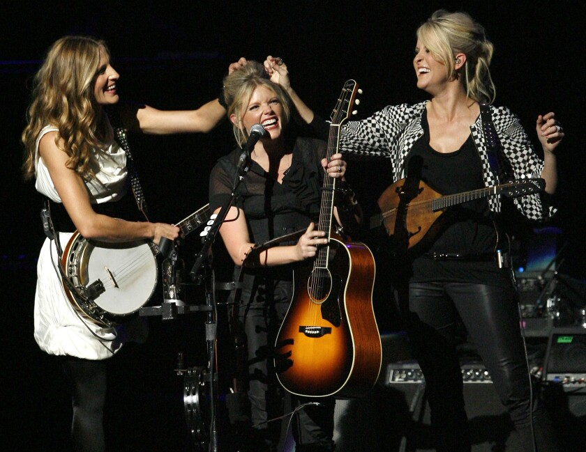 """FILE - In this Oct. 18, 2007 file photo, Emily Robison, left, and Martie Maguire, right, adjust Natalie Maines' hair as the Dixie Chicks perform at the new Nokia Theatre in Los Angeles. The Grammy-winning country group, who recently changed their name to The Chicks, have a new album """"Gaslighter"""" out July 17, 2020. (AP Photo/Gus Ruelas, File)"""