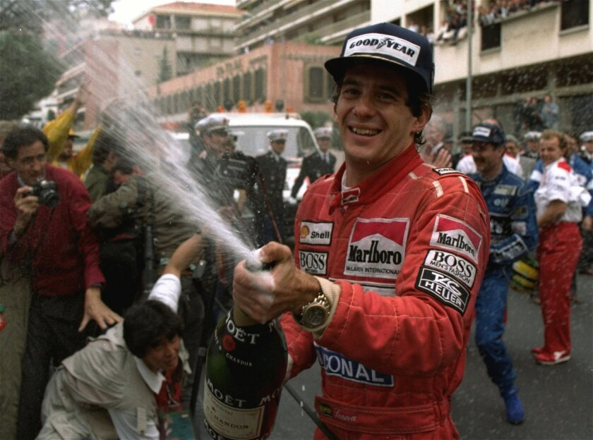 FILE - In this May 12, 1990, file photo, Brazilian driver Ayrton Senna sprays champagne on the photographers to celebrate his career's 30th victory at the Monaco Formula One Grand Prix May 12, 1990. Brazil's adoration of Ayrton Senna transcends sports. It's something only someone like Pele can relish in the country of football. When hundreds of thousands of people lined up for hours just to take a final glimpse of Ayrton Senna's body before his funeral, they were paying tribute to more than a three-time Formula One champion. They were saying farewell to arguably the country's greatest sporting idol. (AP Photo/Lionel Cironneau,File)