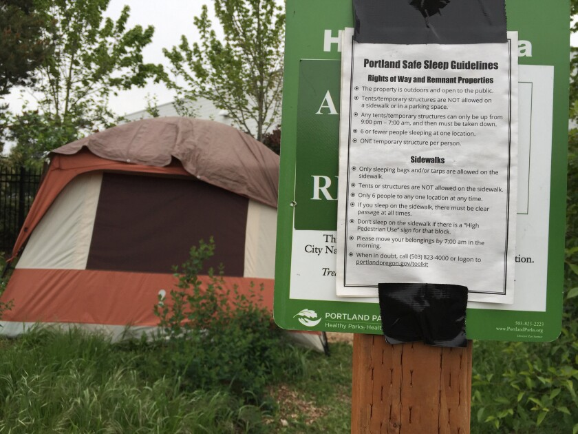 "Portland's ""Safe Sleep Guidelines"" are posted by a homeless encampment."