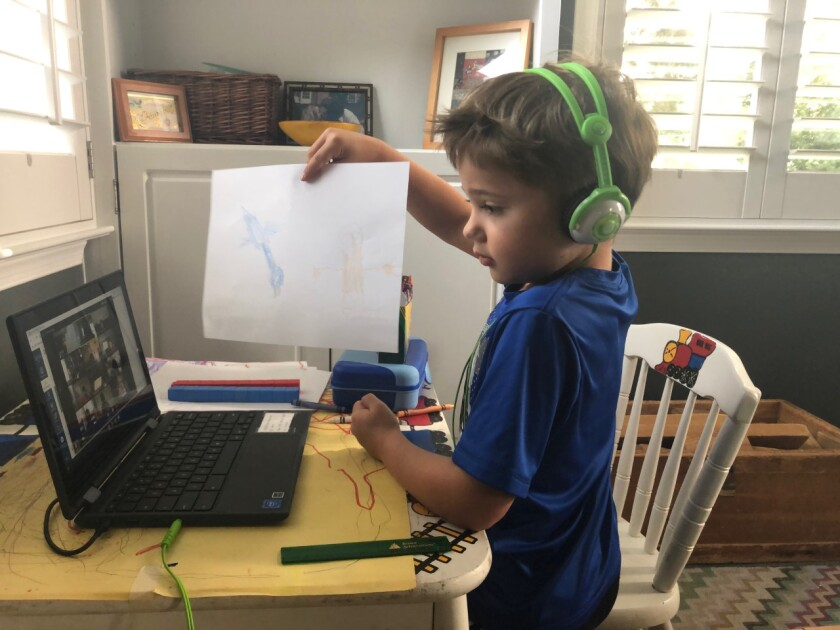 A young boy wearing headphones holds a drawing in front of his laptop camera