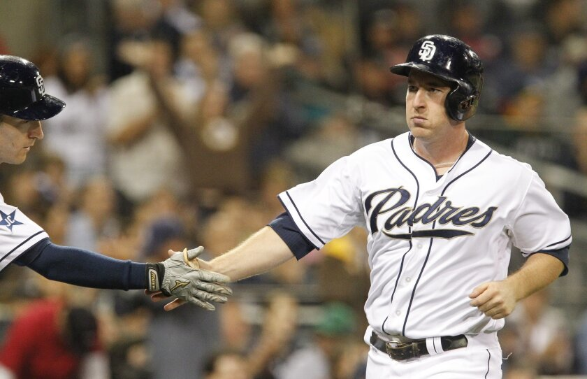 The Padres' Jedd Gyorko, right, is greeted by Chris Denorfia after scoring in the fifth inning.