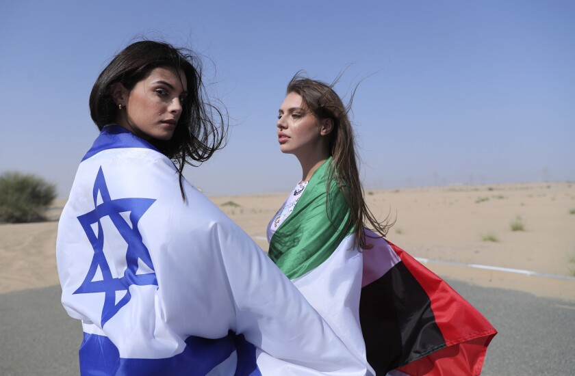 Israeli model May Tager, left, covers herself with an Israeli flag next to Anastasia Bandarenka, a Dubai-based model who covers herself in a UAE flag on the set of a photo shoot in Dubai, United Arab Emirates, Sunday, Sept. 8, 2020. (AP Photo/Kamran Jebreili)
