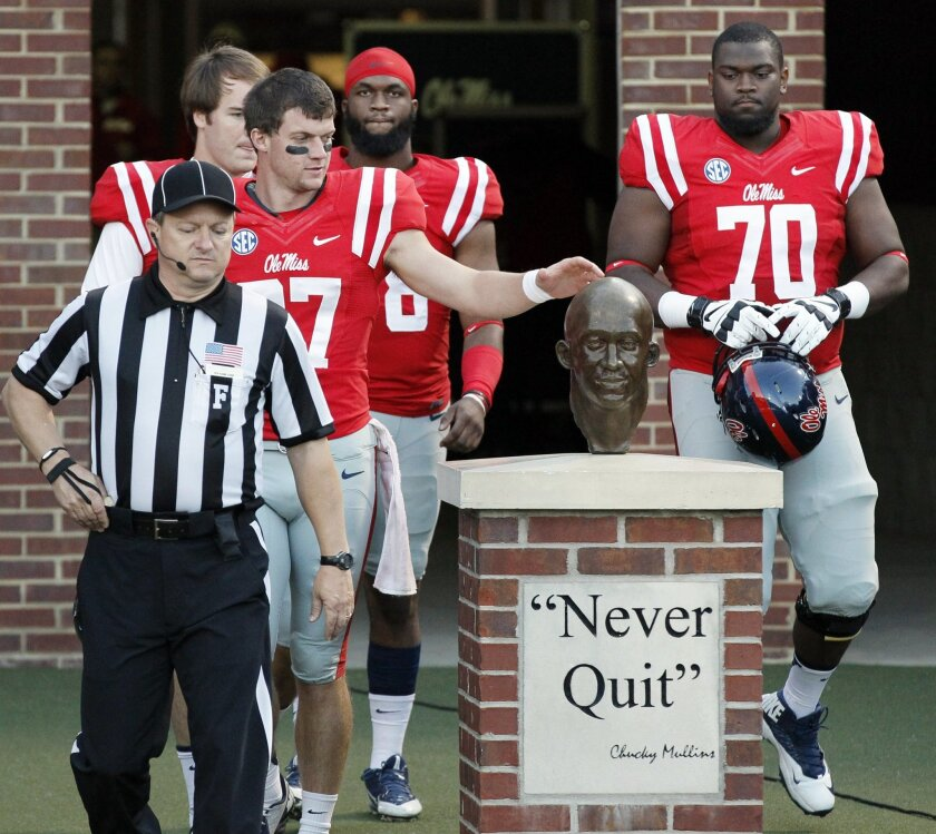 "In this photo taken on Oct. 19, 2013, Mississippi players, including Emmanuel McCray (70), touch the bust of former defensive back Roy Lee ""Chucky"" Mullins for luck before an NCAA college football game against LSU at Vaught-Hemingway Stadium in Oxford, Miss. Mullins suffering a paralyzing neck inju"