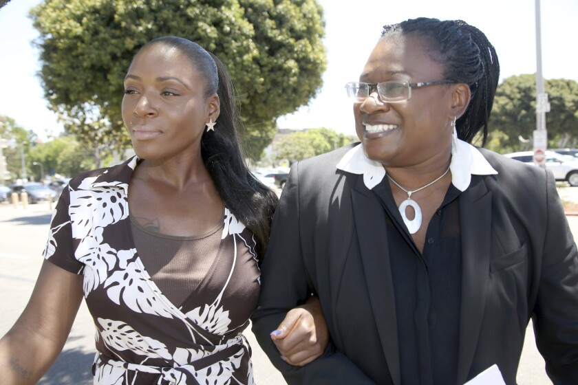 Maisha Allums, left, daughter of Marlene Pinnock, the woman punched by a CHP officer, with attorney Caree Harper before a news conference on Pinnock's lawsuit.