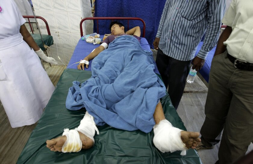 An injured passenger of a train blast receives treatment at a hospital in Chennai, India, Thursday, May 1, 2014. Twin blasts ripped through two coaches of a train Thursday morning just minutes after it pulled into Chennai railway station, killing a 22-year-old woman and injuring 14 people, official