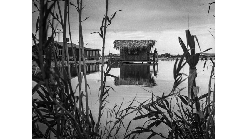 March 27, 1965: Eugene Cowell fishes from Tiki house in his one-acre lake, one of the 35 which have blossomed in the desert community of Newberry Springs.