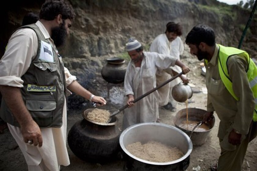 Volunteers of Falah-e-Insaniyat foundation, the charity wing of Pakistan's militant group Jamaat-ud-Dawa supervise the cooking of food for flood affected people in Nowshera in northwest Pakistan on Monday, Aug. 9, 2010. The number of people suffering from the massive floods in Pakistan exceeds 13 m