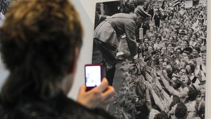 A woman takes a picture of a photograph showing Adolf Hitler with a crowd of supporters in Berlin.