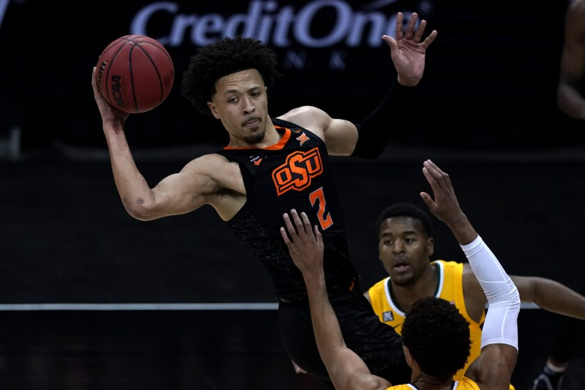 Oklahoma State's Cade Cunningham (2) passes over Baylor's MaCio Teague during the first half of an NCAA college basketball game in the semifinals of the Big 12 tournament in Kansas City, Mo., Friday, March 12, 2021. (AP Photo/Charlie Riedel)