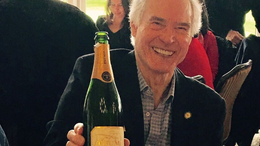 """Sam Hardage, past chair of the county GOP, displays a bottle of Trump Winery sparkling """"blanc de blanc"""" that he and wife, Vivian, shipped in for their inaugural brunch celebration."""