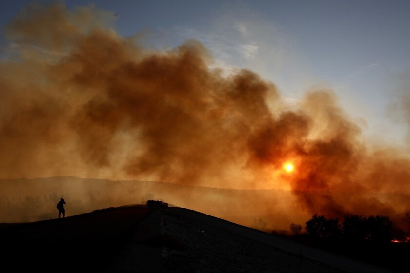 Smoke from a fire obscures the sun