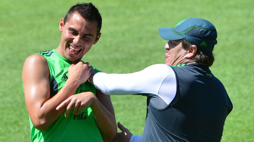 Mexico's Coach Miguel Herrera, right, jokes with defender Paul Aguilar during a team training session Saturday.