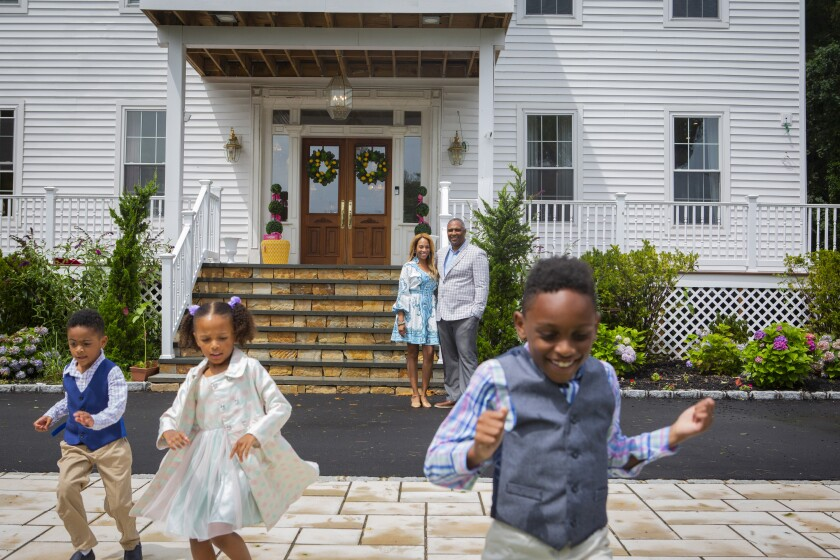 Jamie and Frantz Arty are pictured with their children Fitzgerald and Fallon, 5, and Frantz, 7, outside their house.
