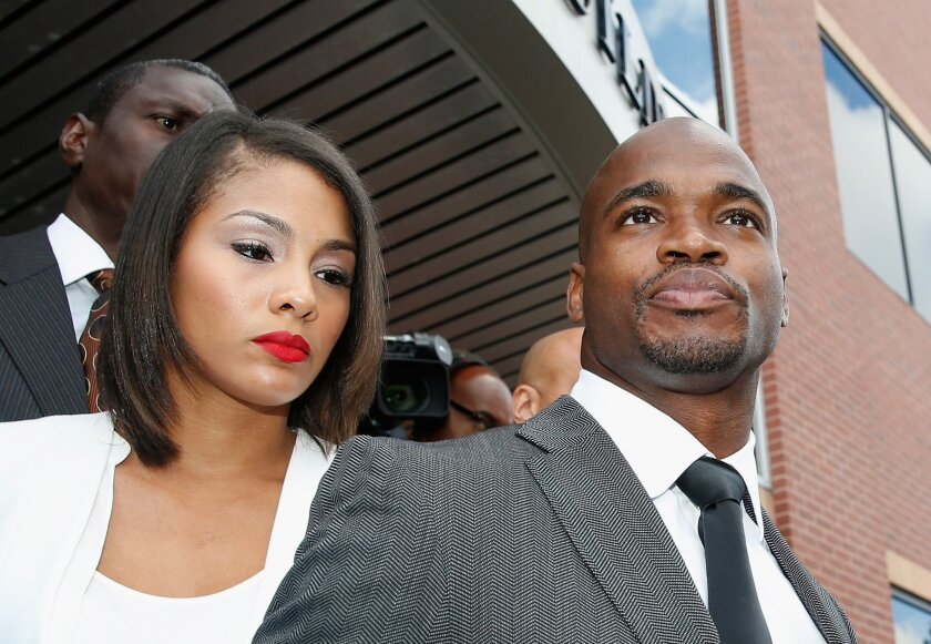 NFL player Adrian Peterson of the Minnesota Vikings waits with his wife Ashley Brown after making a court appearance at the Montgomery County municipal building on Oct. 8, 2014.