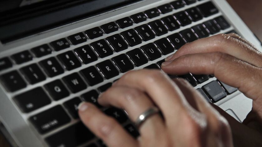 Fingers type on a laptop keyboard Monday, June 19, 2017, in North Andover, Mass. (AP Photo/Elise Ame
