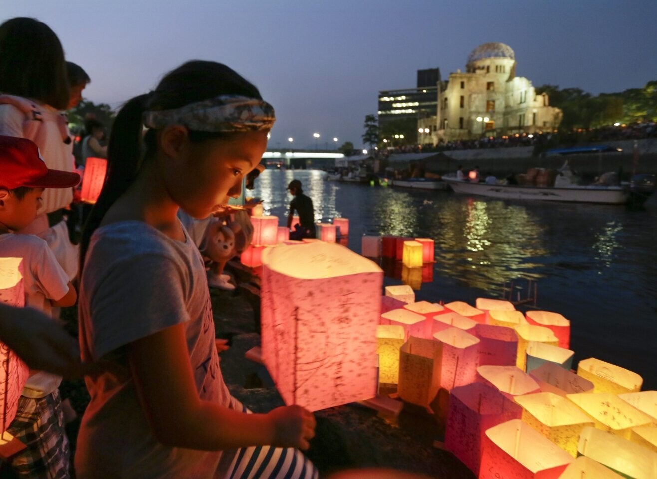 A girl floats a paper lantern on the Motoyasu River to comfort souls of victims killed by the atomic bombing, past the Atomic Bomb Dome at Hiroshima Peace Memorial Peace Park in western Japan.