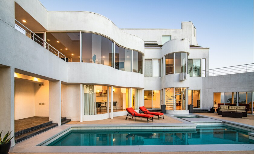 The modern home draws the eye with curving lines and a sleek whitewashed exterior.