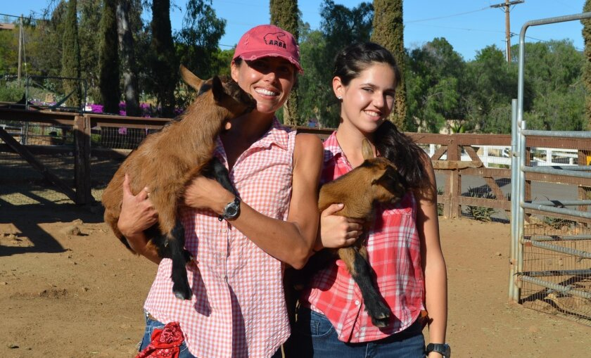 Elizabeth and Sissy Sugarman hold goats at Sugar Sweet Farm in Olivenhain. Volunteers harvested fruit from the farm for St. Andrew's Church food pantry.