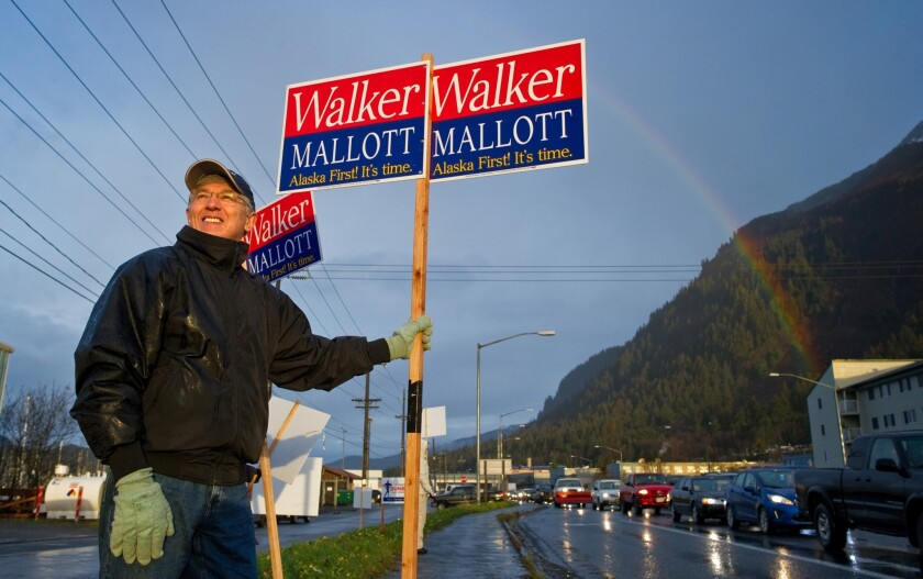 Byron Mallott, a candidate for Alaska lieutenant governor, waves a sign in Juneau on election day. Mallott's running mate is Bill Walker, who narrowly leads Gov. Sean Parnell.