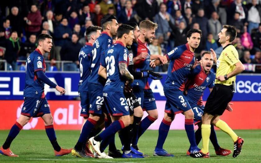 Los jugadores de la SD Huesca protestan al árbitro tras un gol, que fue anulado posteriormente, del Sevilla FC, durante el partido de la 26? jornada de Liga en Primera División en El Alcoraz, en Huesca. EFE
