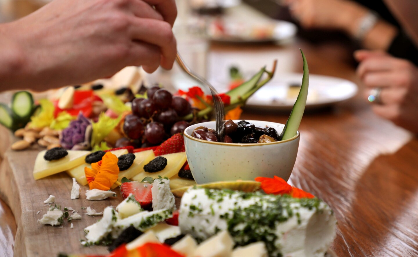 At the Four Season Residence Club a guest at the 10 seat Chef's Table reaches for food from a large Mezze Board (a Mediterranean party platter) that features many types of food.