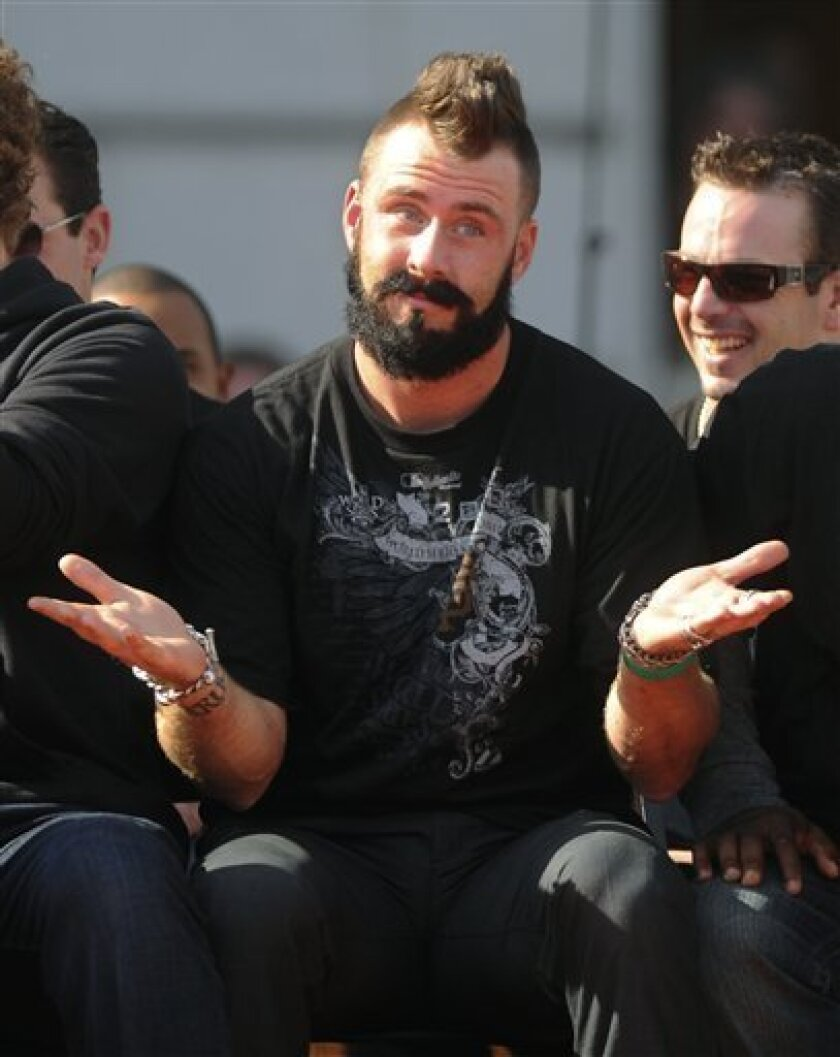 """San Francisco Giants relief pitcher Brian Wilson gestures during a rally for the World Series-champion Giants in front of City Hall in San Francisco on Wednesday, Nov. 3, 2010. The gesture came after California Gov. Arnold Schwarzenegger made a joke about the phrase """"Fear the beard."""" (AP Photo/Noah Berger)"""