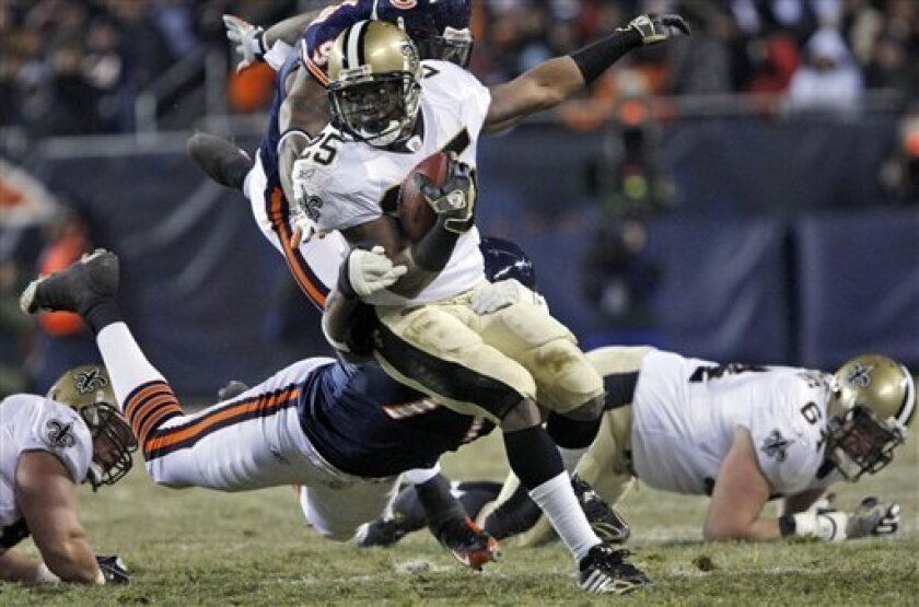 In this Dec. 11, 2008 photo, New Orleans Saints running back Reggie Bush (25) rushes against Chicago Bears defensive lineman Israel Idonije (71) and defensive end Mark Anderson (97) during the first quarter of an NFL football game in Chicago. Bush will miss the final two games of the Saints' season. after he sprained the medial collateral ligament in his left knee during the Saints' loss at Chicago last Thursday night. (AP Photo/Gerald Herbert)