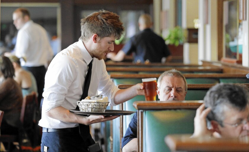 Waiter Spencer Meline serves a customer at Ivar's Acres of Clams restaurant on the Seattle waterfront.