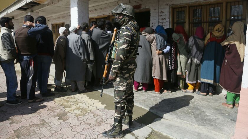 An Indian paramilitary soldier stands guard as Kashmiri voters wait in a queue to cast their votes outside a polling station during the second phase of India's general elections, on the outskirts of Srinagar, Indian-controlled Kashmir, on Thursday.