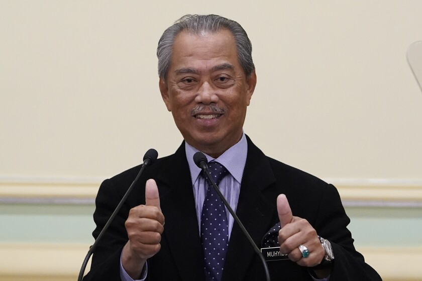 Malaysian new Prime Minister Muhyiddin Yassin, thumbs up during a press conference at prime minister's office in Putrajaya, Malaysia, Monday, March 9, 2020. Muhyiddin unveiled his Cabinet on Monday, saying he will have no deputy but will instead appoint four senior ministers in the move that helped him dodge the tricky issue of succession in his Malay0majority government. (AP Photo/Vincent Thian)