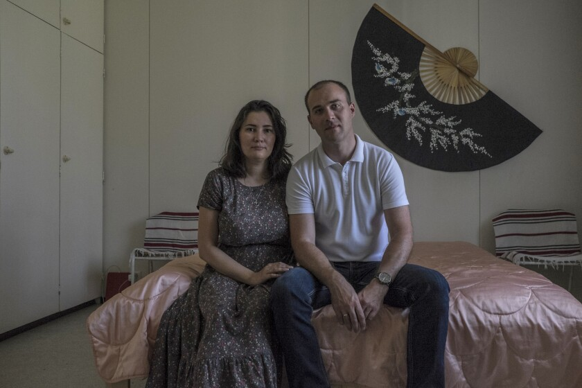 Daniil, 34, and Alina, 35, both from Orenburg, Russia, are posing for a portrait in their room at a