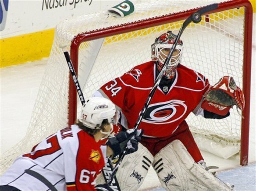 Carolina Hurricanes goalie Manny Legace (34) eyes the puck as Florida Panthers' Michael Frolik (67) attempts to make a play during the first period of an NHL hockey game in Raleigh, N.C., Tuesday, Feb. 9, 2010. (AP Photo/Karl B DeBlaker)