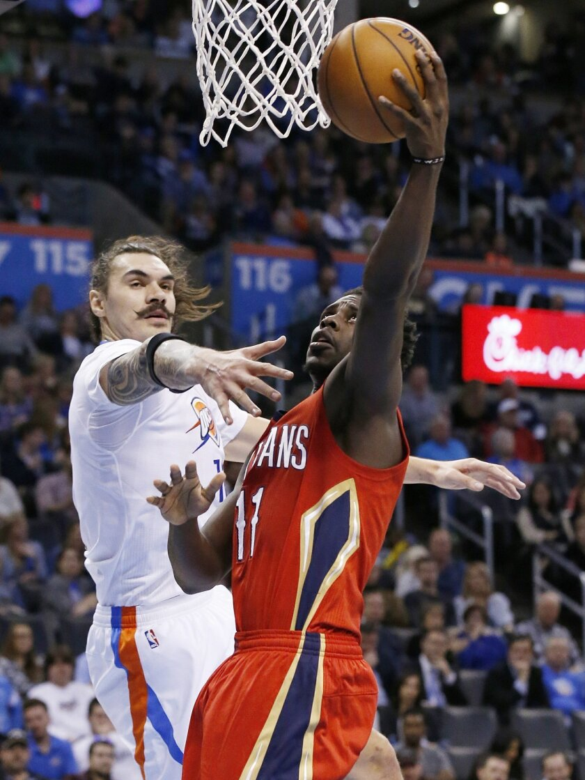 New Orleans Pelicans guard Jrue Holiday (11) shoots as Oklahoma City Thunder center Steven Adams, left, defends, in the second quarter of an NBA basketball game in Oklahoma City, Thursday, Feb. 11, 2016. (AP Photo/Sue Ogrocki)