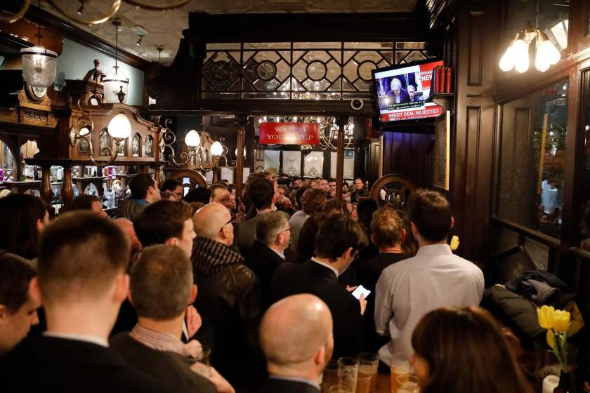 Patrons watch a television screen in the Red Lion public house on Whitehall, as it shows Britain's Prime Minister Theresa May speaking in the Houses of Parliament in London, after MPs vote against the government's Brexit deal.