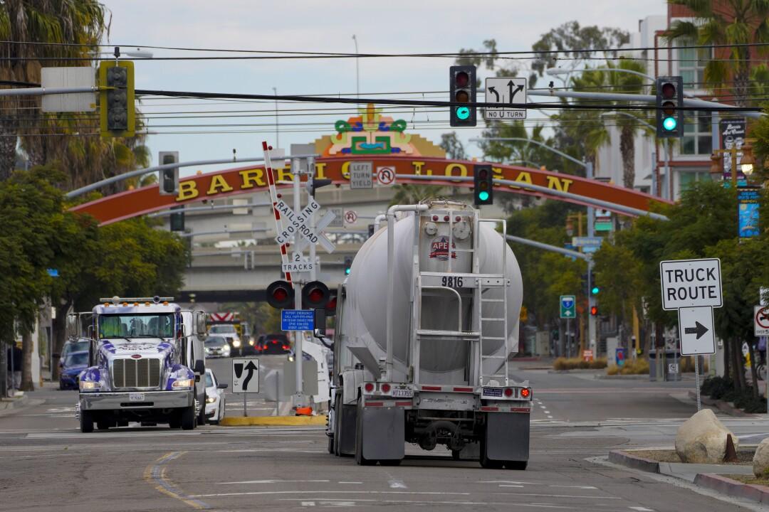 Large semi trucks hauling goods, drive along Harbor Drive and Cesar E. Chavez Parkway in Barrio Logan