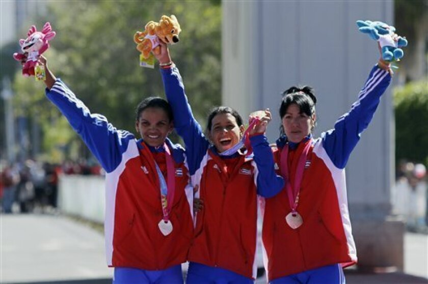 Cuba's silver medal winner Yumari Gonzalez, from left, Cuba's gold medal winner Arlenis Sierra, and Cuba's bronze medal Yudelmis Dominguez, celebrate at the podium during the medal ceremony for the women's cycling road race event at the Pan American Games in Guadalajara, Mexico, Saturday Oct. 22, 2