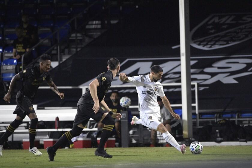 The Galaxy's Sebastian Lletget kicks the ball as LAFC's Mark-Anthony Kaye, far left, and Dejan Jakovic defend July 18.