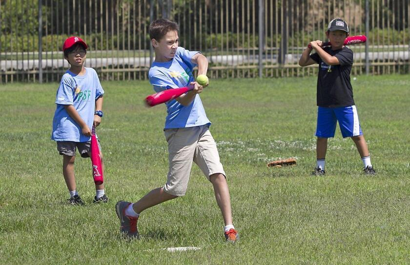 A student in the Science of Baseball class takes a swing for a home run at Stonegate Elementary in Irvine on Thursday.
