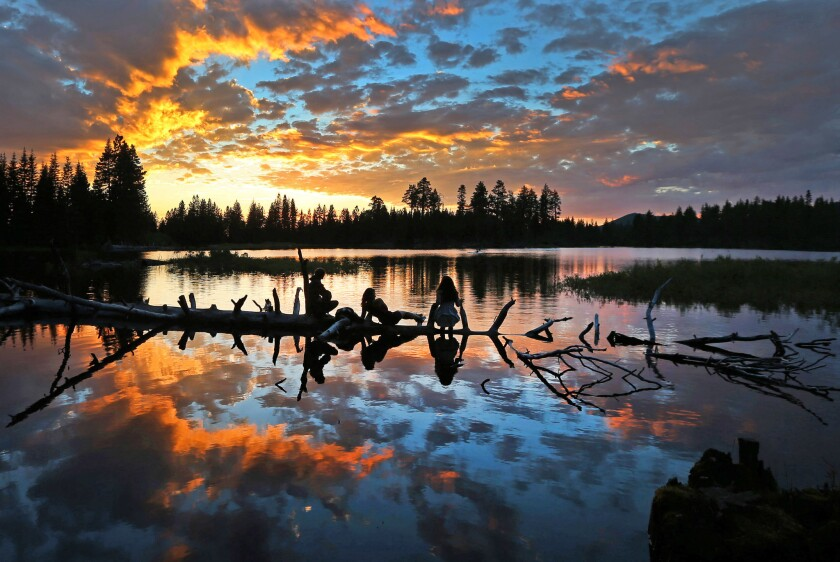 As three young visitors lounge on a fallen tree, sunset falls on Manzanita Lake in Northern California's Lassen Volcanic National Park.