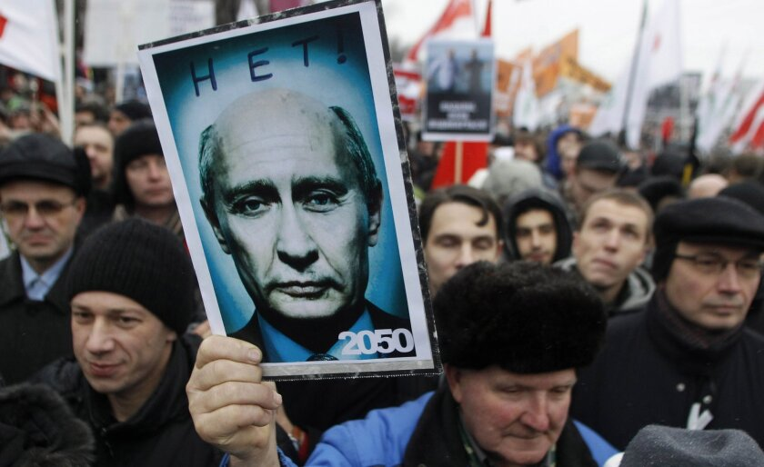 A demonstrator holds a poster showing a manipulated photograph of Russian Prime Minister Vladimir Pu