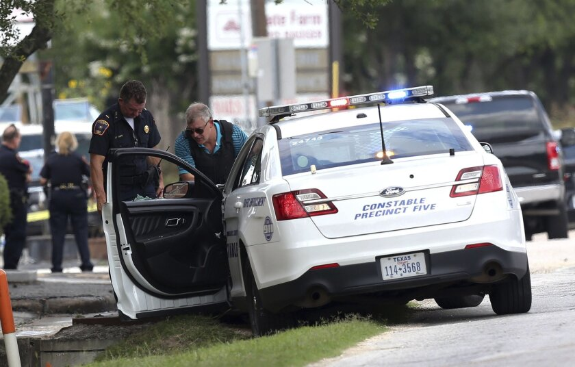 A C=constable car with a shot-out window remains at the scene where Houston police were investigating a shooting, Sunday, May 29, 2016, in Houston. A man came into an auto detail shop and began shooting, killing a man known to be a customer and putting a neighborhood on lockdown before being killed