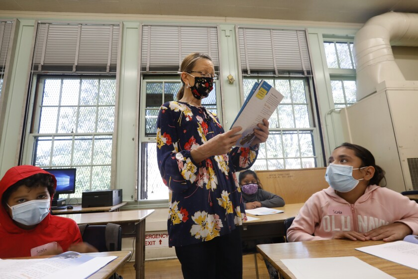 A teacher stands in class between two students. All are wearing masks.