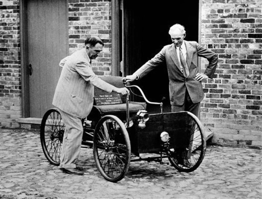 FILE - In this Dec. 10, 1936 file photo, Henry Ford, right, stands with his first car built in 1892, assembled in the brick barn in the background in Detroit. At left is James Bishop. (AP Photo)