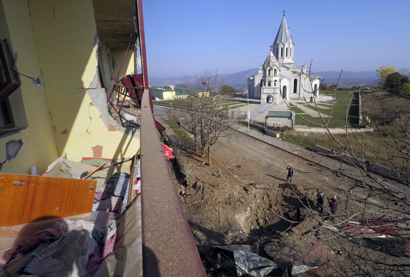 Men examine a bomb crater near the Holy Savior Cathedral in Nagorno-Karabakh after shelling by Azerbaijan's forces.