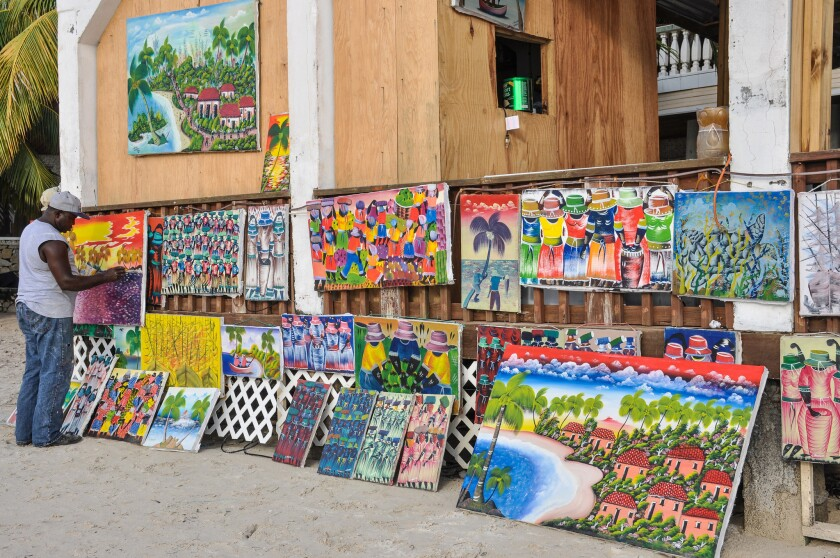 An artist paints colorful Caribbean canvases on West Bay beach.