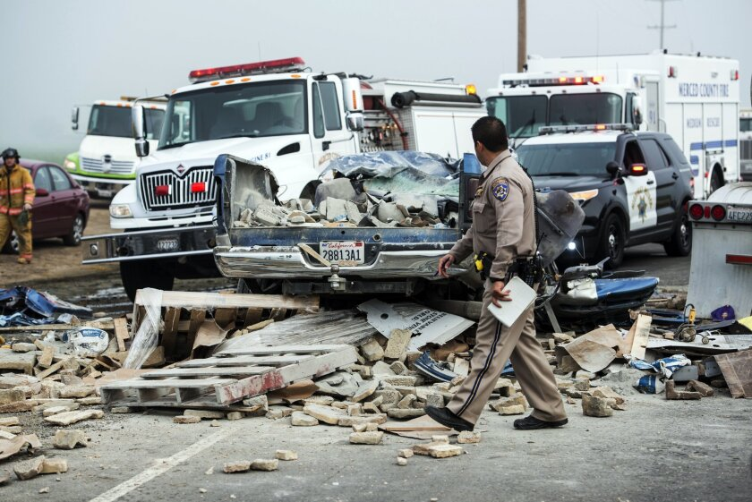 Emergency personnel work at the scene of a crash, one of several separate collisions, on Highway 59 in Merced County, Calif., Saturday, Feb. 13, 2016. The CHP says there was fog on the highway around the time of the crashes, but the cause remains under investigation. (Andrew Kuhn/Merced Sun-Star vi