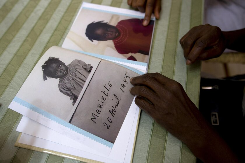 In this July 13, 2015 photo, during a visit with her birth mother and other family, in Port-au-Prince, Haiti, adoptee Mariette Williams shows pictures of herself, made when she was living at a Haitian orphanage in the mid 80's. For the first time in nearly 30 years, Mariette was reunited with her b