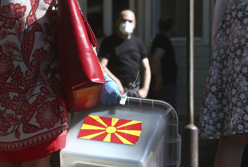 A woman carries a ballot box at a municipal election commission headquarters making final arrangements prior to visiting voters who have tested positive for COVID-19 or are in self-isolation, in Skopje, North Macedonia on Monday, July 13, 2020. North Macedonia holds its first parliamentary election under its new country name this week, with voters heading to the polls during an alarming spike of coronavirus cases in the small Balkan nation. Opinion polls in the run-up to Wednesday's vote indicate a close race between coalitions led by the Social Democrats and the center-right opposition VMRO-DPMNE party. (AP Photo/Boris Grdanoski)