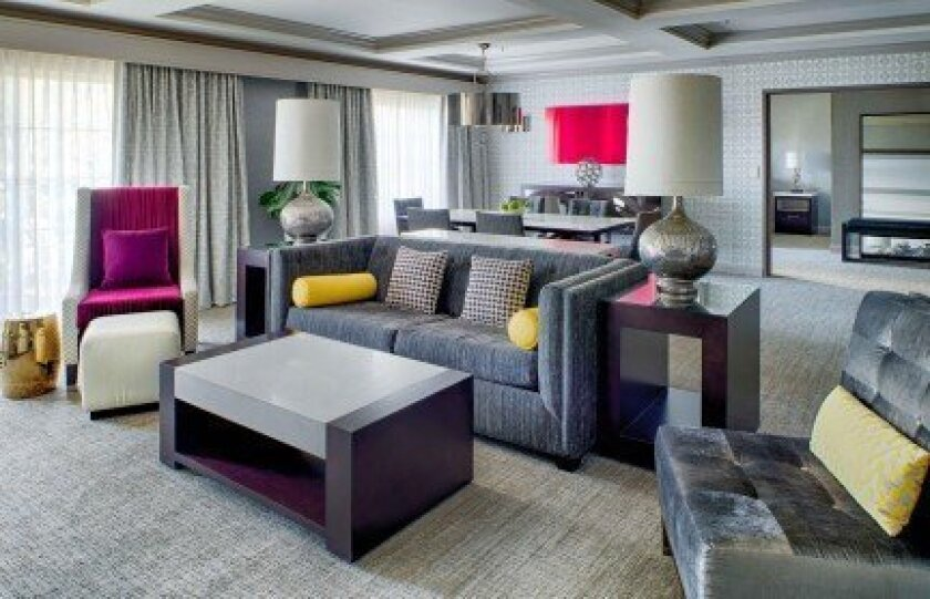 The living room in a suite has touches of magenta and red to accent the gray tones.